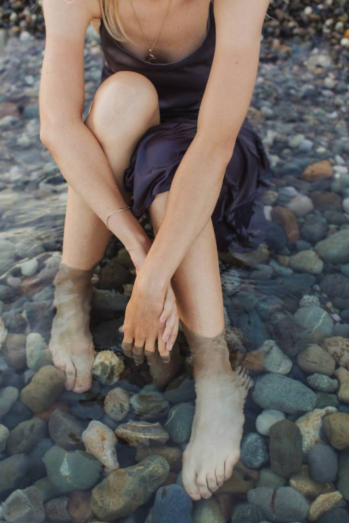 Abundance of Water - Woman With Feet in Water on Rocky Shore