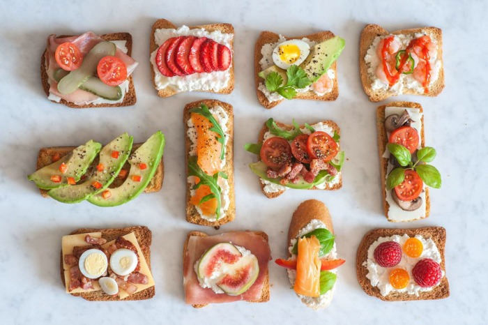 Beautiful food items on toast arranged on a table.