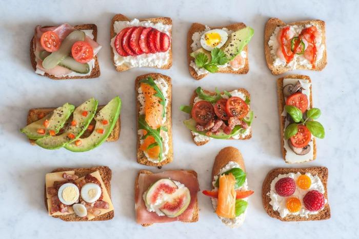 Beautiful food items on toast arranged on a table.